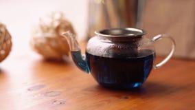 De vrouw opent en sluit het deksel van de theepot met hete Bloemen blauwe Thaise thee