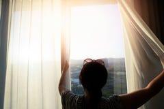 De vrouw opent het gordijn bij het venster in de ochtend royalty-vrije stock foto