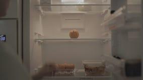 De vrouw opent koelkast, zet citroen daarin en sluit het stock videobeelden