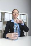 De vrouw opent waterfles in bureau Stock Fotografie