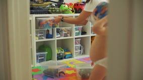 De vrouw organiseert Speelgoed en de Baby probeert op Kleren stock videobeelden