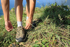 De vrouw overhandigt bindende schoenveter op mountian kust Royalty-vrije Stock Fotografie