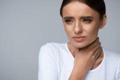 De vrouw overhandigt de zieke plaats Zieke Vrouw die aan Pijn, het Pijnlijke Slikken lijden Royalty-vrije Stock Foto
