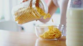 De vrouw overhandigt gietende cornflakes in glaskom Sluit omhoog het voorbereiden van graangewassen stock footage