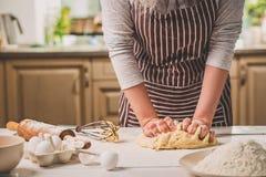 De vrouw overhandigt het kneden deeg op keukenlijst royalty-vrije stock foto's