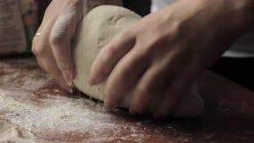De vrouw overhandigt het kneden deeg op lijst kokend voedsel op een keuken stock video