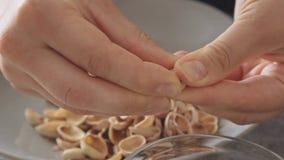 De vrouw overhandigt het openen pistaches boven glaskom stock video