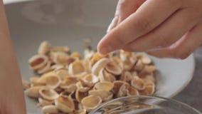 De vrouw overhandigt het openen pistaches boven glaskom stock footage