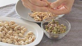 De vrouw overhandigt het openen pistaches boven glaskom stock videobeelden