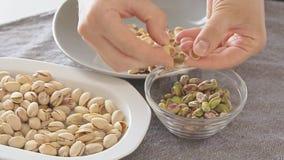 De vrouw overhandigt het openen pistaches boven kom stock videobeelden