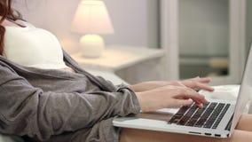 De vrouw overhandigt het typen laptop toetsenbord in bed Vrouwelijke handen die toetsenbord typen stock footage