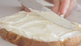 De vrouw overhandigt het uitspreiden kaas op broodplak stock video