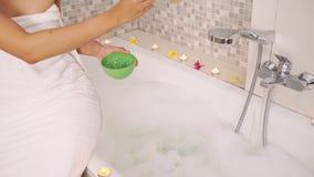 De vrouw overhandigt het uitspreiden kuuroordzout in badkuip stock footage
