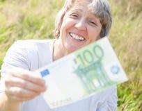 De vrouw overhandigt honderd euro Stock Foto's