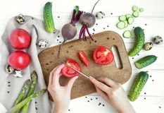 De vrouw overhandigt snijdende tomaat op houten scherpe die raad, door groenten wordt omringd Vlak leg, hoogste mening royalty-vrije stock foto