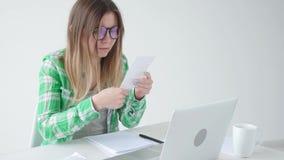 De vrouw overweegt de hoeveelheid uitgaven voor aankopen en betaling van kredieten door informatie in laptop voor in te gaan stock videobeelden