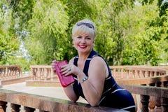 De vrouw in park met een rode handtas Stock Foto's