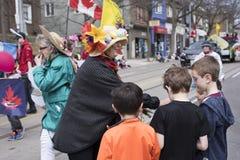 De vrouw in Pasen-kostuum verdeelt giften aan kinderen langs Royalty-vrije Stock Afbeelding