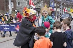 De vrouw in Pasen-kostuum verdeelt giften aan kinderen langs Royalty-vrije Stock Foto