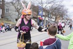 De vrouw in Pasen-kostuum verdeelt giften aan kinderen langs de Koningin Street East in de Parade 2017 van Strandenpasen Stock Foto