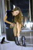 De vrouw past op laarzen in een boutique Royalty-vrije Stock Afbeeldingen