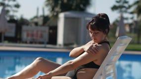 De vrouw past zorgvuldig bevochtigende lotion op lichaam toe die rust dichtbij zwembad hebben stock footage