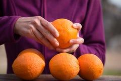 De vrouw pelt sinaasappelen van schil stock fotografie