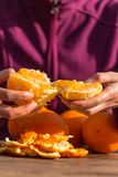 De vrouw pelt sinaasappelen van schil royalty-vrije stock afbeelding