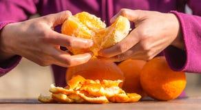 De vrouw pelt sinaasappelen van schil stock foto's