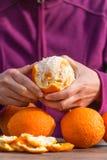 De vrouw pelt sinaasappelen van schil royalty-vrije stock afbeeldingen