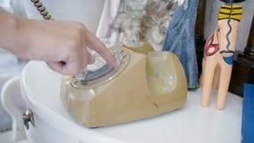 De vrouw plukt oude roterende stijltelefoon op de lijst met wijnoogst met de hand verfraait stijl en het draaien omhoog telefoona stock videobeelden