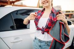 De vrouw poetst auto na was bij de autowasserette op royalty-vrije stock afbeelding