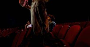 De vrouw popcorn hebben en de koude die drinken terwijl het letten van op film 4k stock videobeelden
