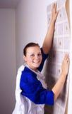 De vrouw probeert op behang aan muur Stock Afbeelding