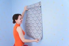 De vrouw probeert op behang aan muur Royalty-vrije Stock Afbeeldingen