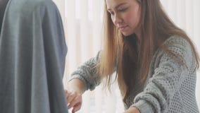 de vrouw probeert op kleding op een ledenpop en brengt veranderingen aan stock videobeelden