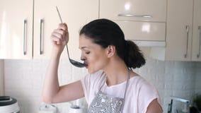 De vrouw proeft soep alvorens te dienen stock video