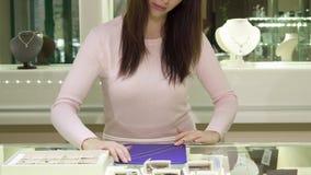 De vrouw raakt halsband bij de boutique stock video
