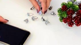 De vrouw raakt juwelen van kostbare en onedele metalen, glas, sierstenen, Topaas en maansteen, smartphone worden gemaakt die stock footage