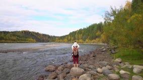 De vrouw de reiziger kost op de bank van de bergrivier Daling stock videobeelden