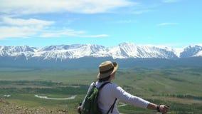 De vrouw de reiziger met een groene rugzak kost op de heuvel en bekijkt witte bergen stock footage