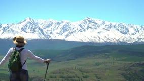De vrouw de reiziger met een groene rugzak kost op de heuvel en bekijkt witte bergen stock video