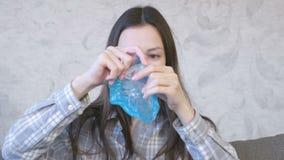 De vrouw rekt een blauwe slijmzitting op de bus en het spelen uit Het kijken door het slijm stock videobeelden