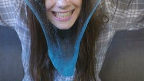 De vrouw rekt een het blauwe slijm en spelen uit Close-uphanden stock video