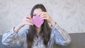 De vrouw rekt een roze slijmzitting op de bus en het spelen uit Het kijken door het slijm stock video