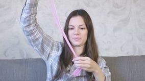 De vrouw rekt een roze slijmzitting op de bus en het spelen uit Het kijken door het slijm stock videobeelden