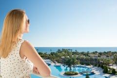 De vrouw richt met haar vinger aan het overzees van balkony in de zomervakantie royalty-vrije stock afbeelding
