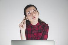 De vrouw in rode geruite kleding denkt over project stock fotografie