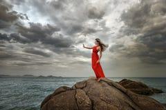 De vrouw in rode kleding bevindt zich op een klip met een mooie overzeese mening a Royalty-vrije Stock Foto