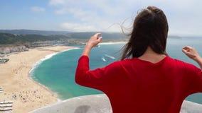 De vrouw in rode kleding geniet van een mening van de oceaankust dichtbij Nazare, Portugal stock videobeelden